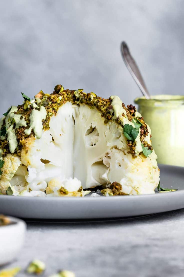 This pistachio-crusted whole roasted cauliflower is so easy to make it's deceptively gourmet! Drizzled with parsley pistachio cream sauce, this loaded cauliflower is perfect as a vegetarian main dish show stopper or a weeknight side dish.  #pistachio #cauliflower #wholeroastedcauliflower #pistachiocrusted #vegan #vegetarian #maincourse #entree #recipe